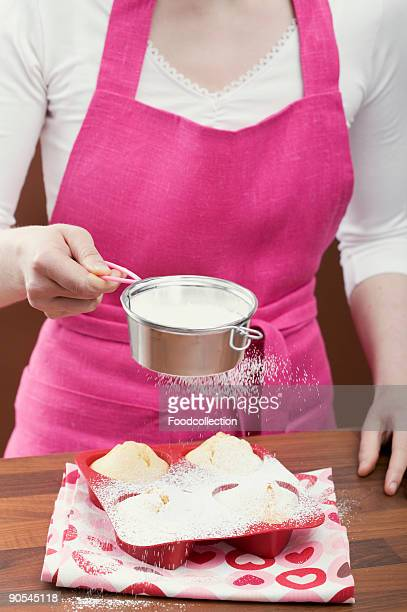 Young woman sprinkling icing sugar over muffins, close up
