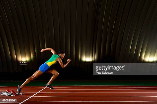 Young woman sprinting from starting blocks in stadium