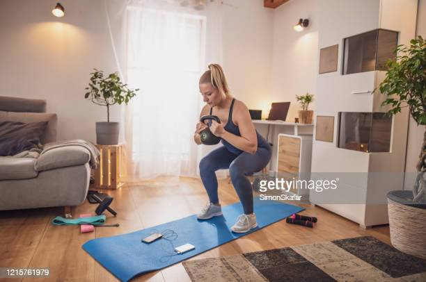 young woman squatting with kettlebell on yoga mat in living room - sports training stock pictures, royalty-free photos & images