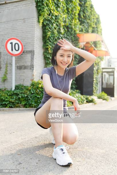 young woman squatting with one knee down - down on one knee stock pictures, royalty-free photos & images
