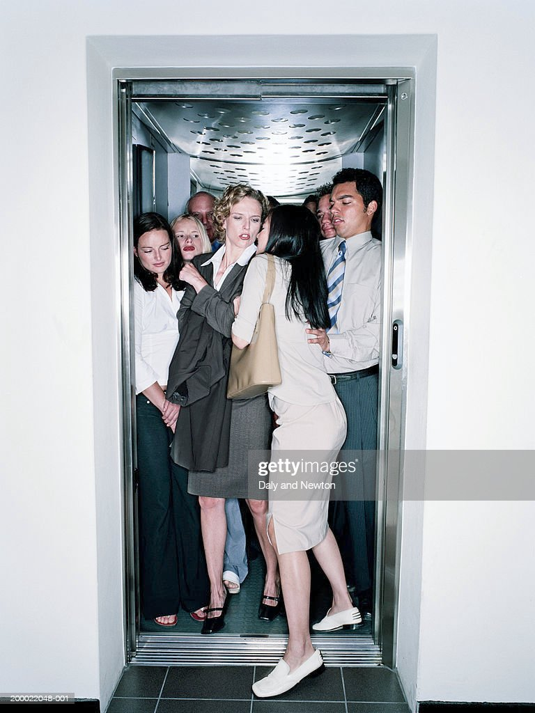 Young woman squeezing into crowded lift : Stock Photo
