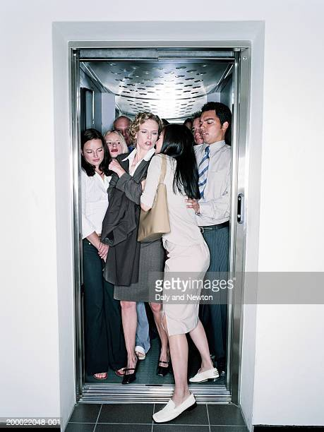 young woman squeezing into crowded lift - full stock pictures, royalty-free photos & images