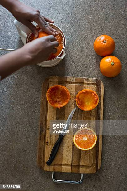 Young woman squeezing orange juice