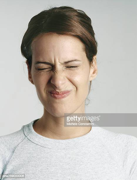 young woman squinting eyes shut, close-up - weigeren stockfoto's en -beelden