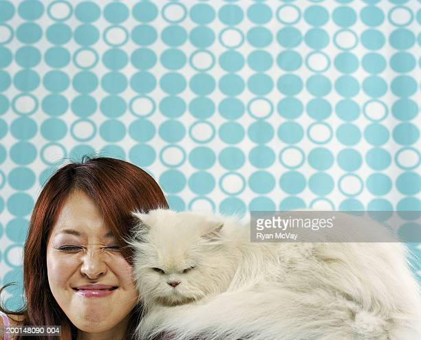 Young woman squinting next to Persian cat
