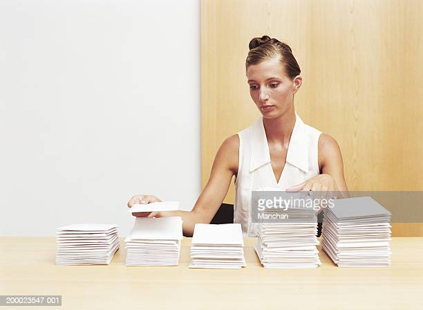 Young woman stacking envelopes on desk