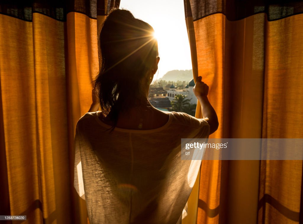 Young woman stand in the room open curtain seeing the beautiful sunrise : Stock Photo
