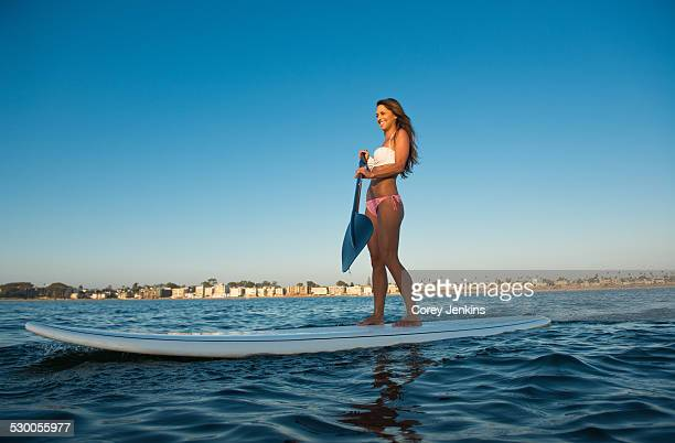 Young woman stand up paddleboarding, Mission Bay, San Diego, California, USA
