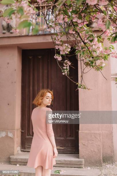young woman standing against closed door - pink dress stock pictures, royalty-free photos & images
