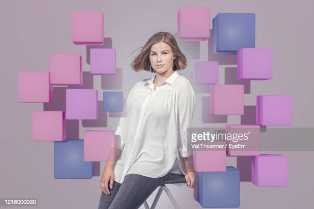 young woman standing against gray background - val thoermer stock-fotos und bilder
