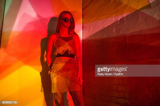 Young Woman Standing Against Illuminated Wall