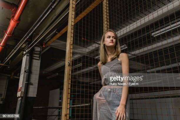 Young Woman Standing Against Metal Grate