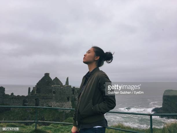 Young Woman Standing Against Old Ruins By Sea