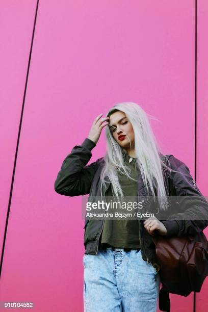young woman standing against pink wall - white hair stock pictures, royalty-free photos & images