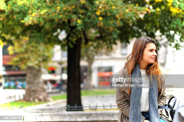 young woman standing against trees in city - neckwear stock pictures, royalty-free photos & images
