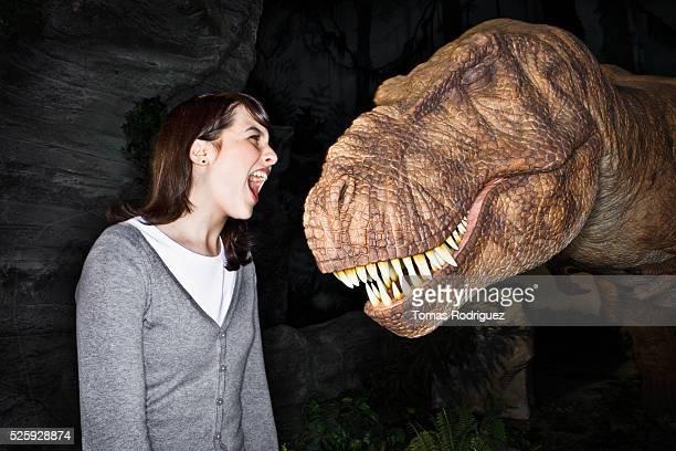 young woman standing against tyrannosaurus rex and screaming - t rex stock-fotos und bilder