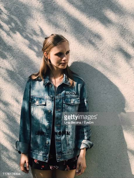 young woman standing against wall - una persona stock pictures, royalty-free photos & images