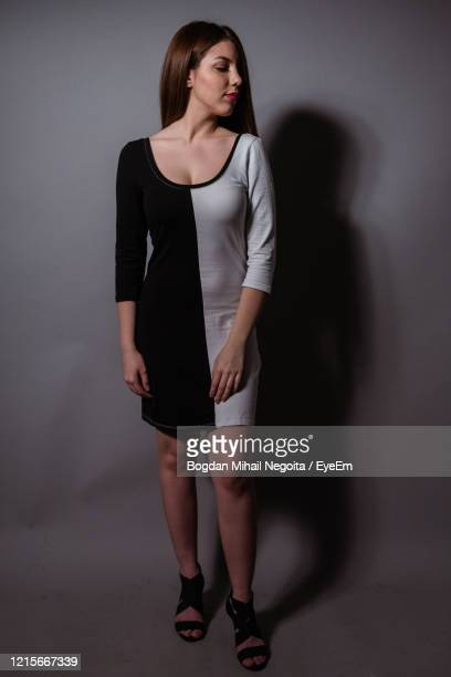 young woman standing against wall - bogdan negoita stock pictures, royalty-free photos & images