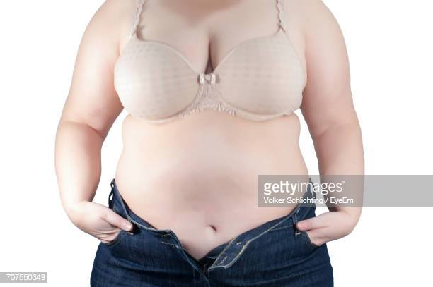 young woman standing against white background - female navel stock photos and pictures