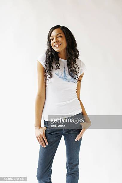 Young woman standing against white background with thumbs in pockets, portrait