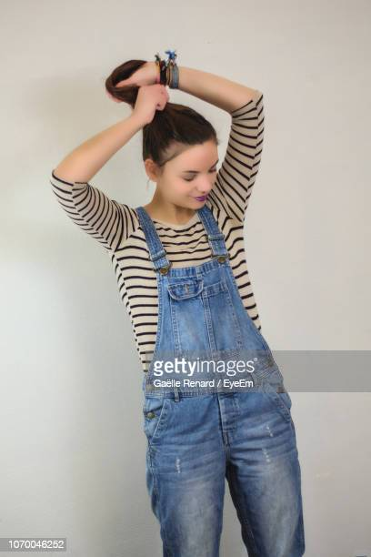 young woman standing against white wall - dungarees stock pictures, royalty-free photos & images