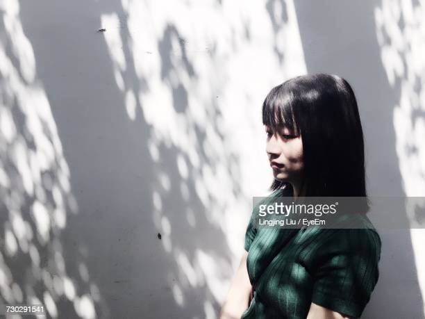 young woman standing against white wall - schaduw stockfoto's en -beelden