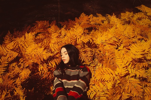 Young Woman Standing Against Yellow Autumn Plants - gettyimageskorea