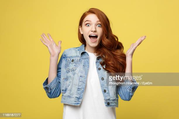 young woman standing against yellow background - surprise stock pictures, royalty-free photos & images
