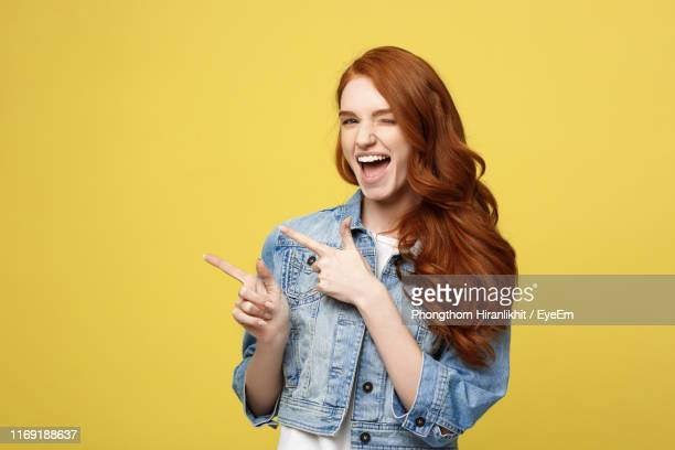 young woman standing against yellow background - mit dem finger zeigen stock-fotos und bilder