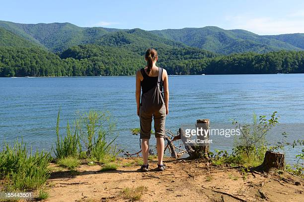 Young woman standing alone and looking out at Watauga Lake
