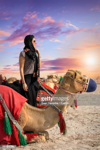 young woman standing amidst camels at desert against sky during sunset - hot arab women stock photos and pictures