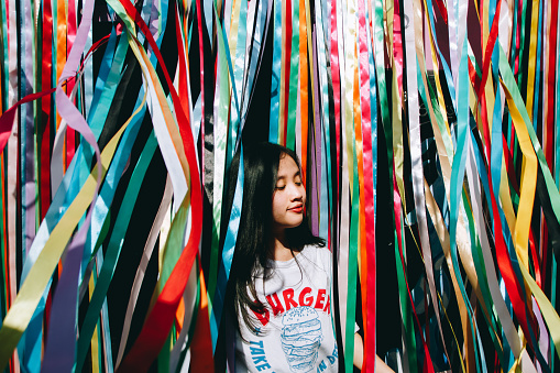 Young Woman Standing Amidst Colorful Ribbons - gettyimageskorea