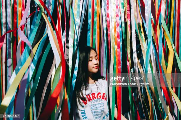 Young Woman Standing Amidst Colorful Ribbons