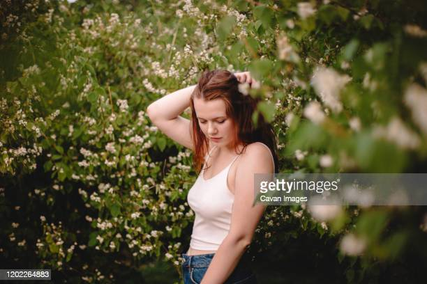 young woman standing amidst flowering branches in park during spring - braless women stockfoto's en -beelden