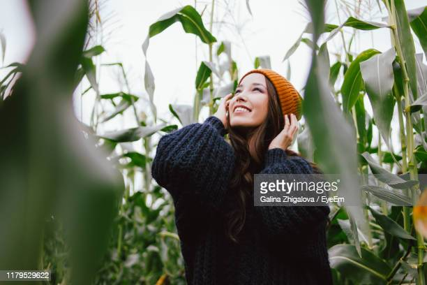 young woman standing amidst plants - front view stock pictures, royalty-free photos & images