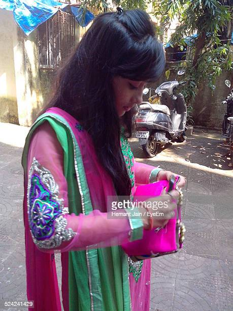 young woman standing and opening purse - salwar kameez stock photos and pictures