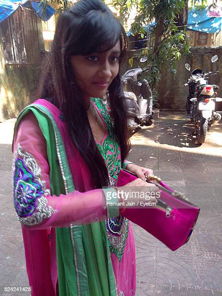 young woman standing and opening purse while looking away - salwar kameez stock pictures, royalty-free photos & images