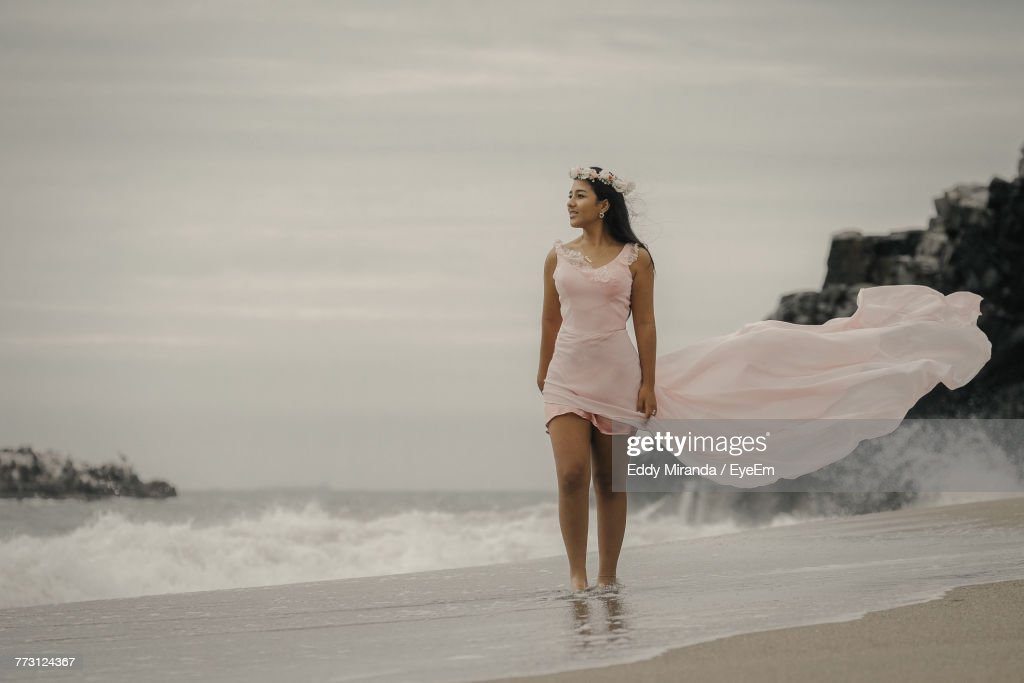 Young Woman Standing At Beach Against Sky : Photo