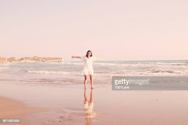 Young woman standing at beach. Freedom concept. Elegance at sunset.