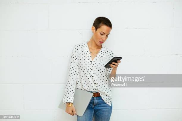 young woman standing at brick wall looking on cell phone - chemisier photos et images de collection