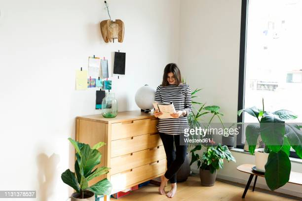 young woman standing at commode at home reading a booklet - woman flat chest stock photos and pictures