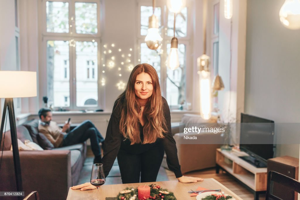 young woman standing at dining table with christmas decoration : Stock Photo