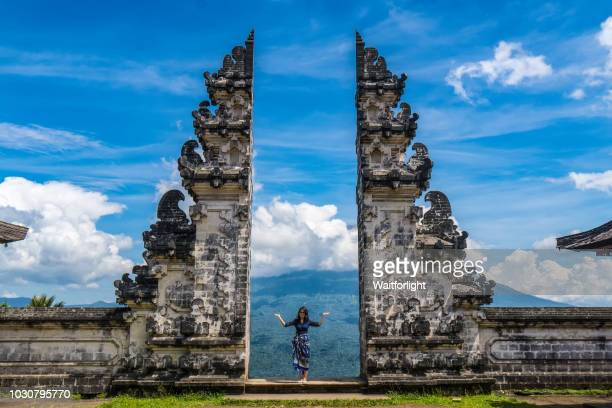 young woman standing at gate to heaven,pura lempuyang temple,bali,indonesia - tempel stock-fotos und bilder