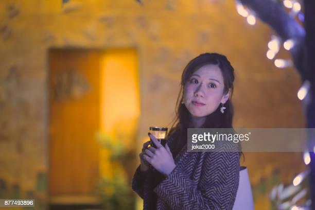 クリスマスの照明を通り decolatd に立っている若い女性