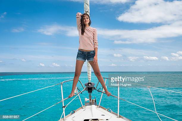 young woman standing at the bow of sailboat - denim shorts stock pictures, royalty-free photos & images