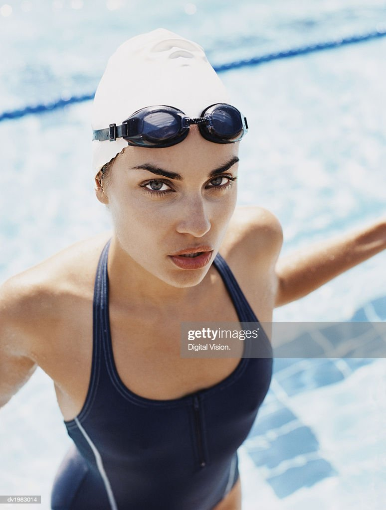 Young Woman Standing at the Edge of a Swimming Pool : Stock Photo