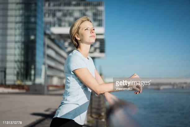 young woman standing at the riverside, enjoying the sun - もたれる ストックフォトと画像