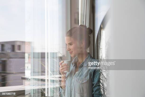 Young woman standing at the window, drinking coffee
