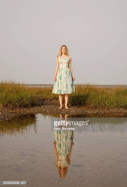 Young woman standing at waters edge on meadow