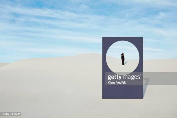 young woman standing at white desert seen through window frame - individuality fotografías e imágenes de stock